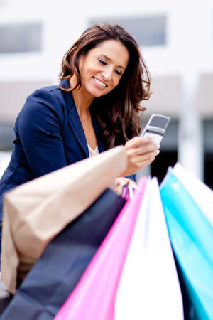 Woman texting on her cell phone while shopping photo