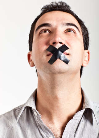 Silenced man with tape on his mouth - isolated over a white background photo