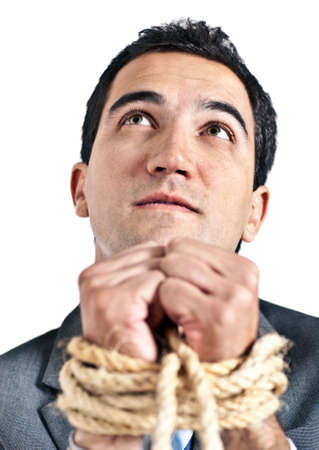 Tortured business man holding his hands tied with a rope  photo