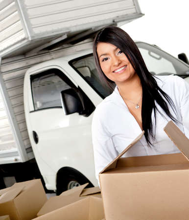 moving house: Woman moving house carrying boxes - isolated over a white background Stock Photo