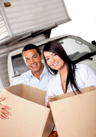Couple moving house carrying boxes with a truck behind Stock Photo - 12198171
