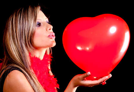 Woman celebrating Valentines Day kissing a heart shaped balloon  photo