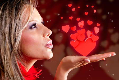 amorous woman: Woman celebrating Valentines day blowing red hearts  Stock Photo