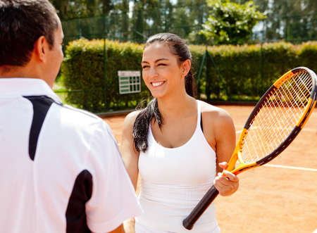 Couple handshaking at the tennis court after playing a game  photo