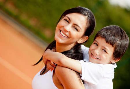 mamma e figlio: Ritratto di una madre bella e figlio al campo da tennis