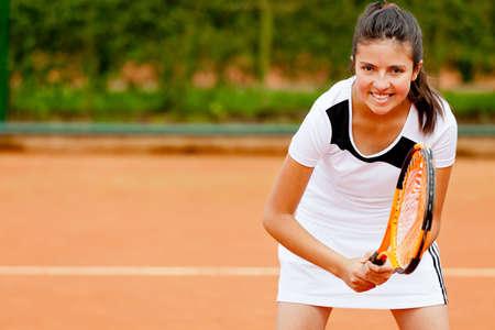 jugando tenis: Chica jugando al tenis en una cancha de arcilla celebraci�n de la raqueta