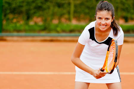 tennis clay: Girl playing tennis at a clay court holding the racket