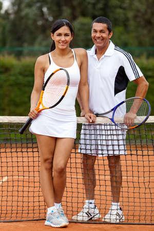 jugando tenis: Pareja en la cancha de tenis y raquetas de la celebraci�n de Foto de archivo