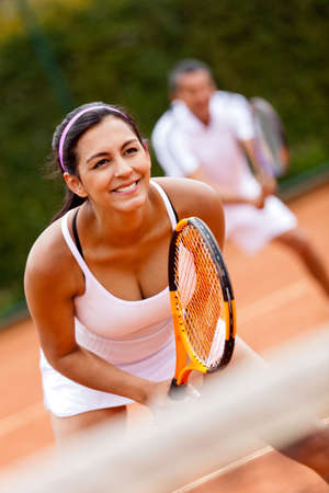 Couple playing doubles at the tennis court  photo