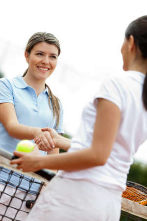 Women handshaking after playing a tennis match  photo