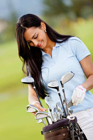 Female golf player with a bag at the course  Stock Photo - 12197697