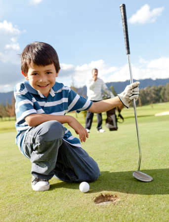 Young boy playing golf at the club  photo