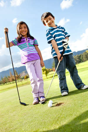 Kids at the course playing golf and looking happy photo