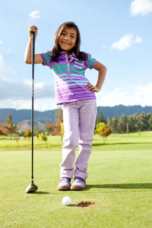 Beautiful girl playing golf looking very happy  photo