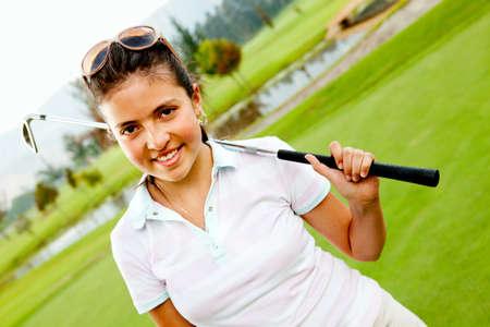 teen golf: Chica en el campo de la pr�ctica del golf y la celebraci�n de un club