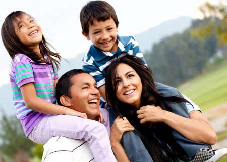 hispanic kids: Beautiful family portrait outdoors looking very happy