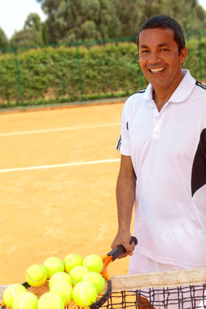 Male tennis player at a clay court holding racket with balls photo