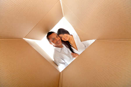 Couple in a cardboard box ready to move house photo