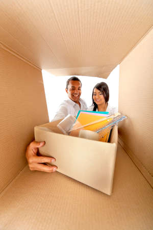 Couple packing in cardboard boxes to move house photo