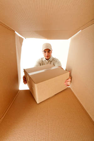 Delivery man holding a package inside a cardboard box Stock Photo - 12198283
