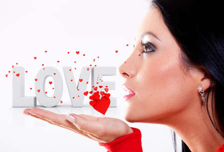 love blow: Woman in love blowing hearts – isolated over a white background