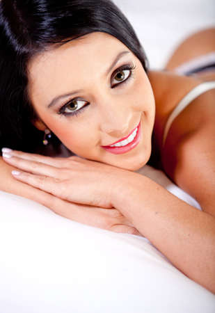 Sexy woman lying on the bed smiling  photo