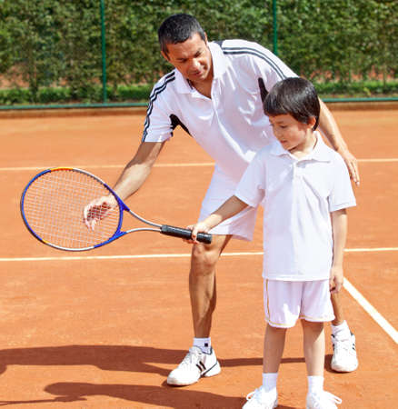 playing tennis: Father teaching his son how to playing tennis