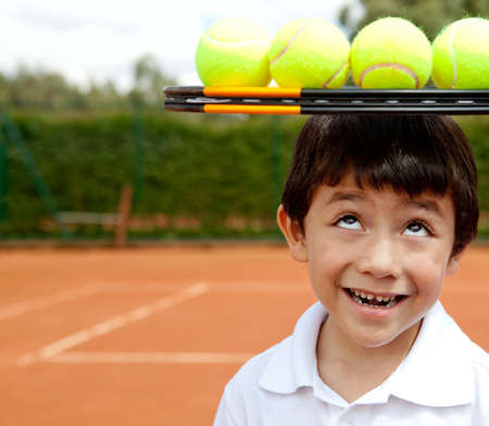 Male tennis player a racket and balls on top of his head  photo