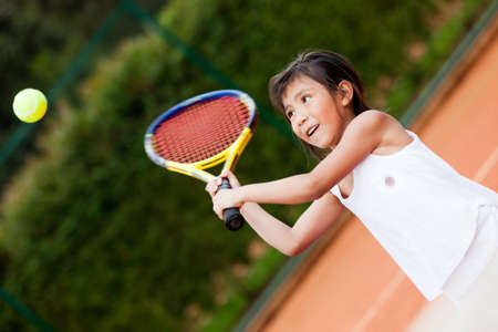 playing tennis: Little girl playing tennis at a clay court