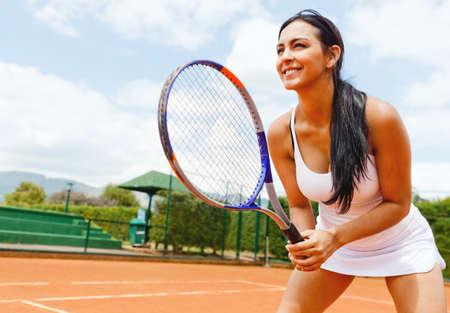jugando tenis: Mujer jugando al tenis y esperar a que el servicio
