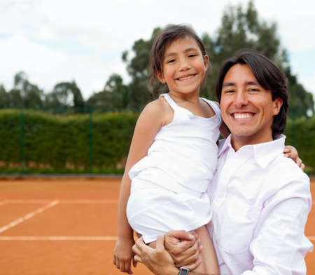 Family portrait at a clay tennis court smiling photo