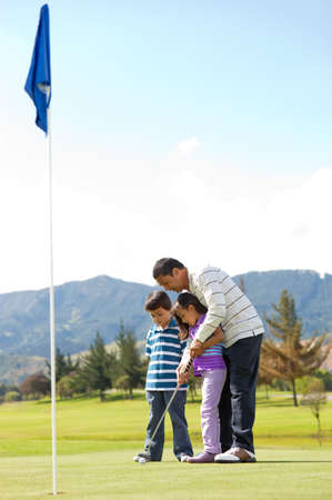 Father teaching his kids how to playing golf photo