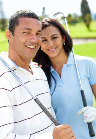 Happy couple playing golf at the club photo