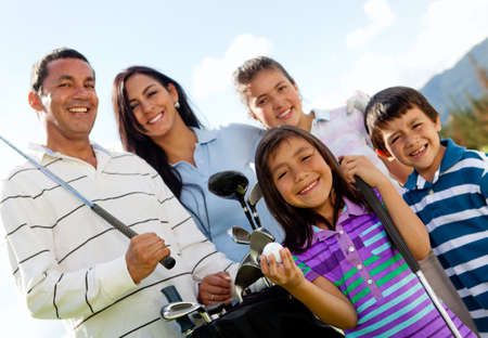 woman golf: Portrait of a beautiful happy family playing golf