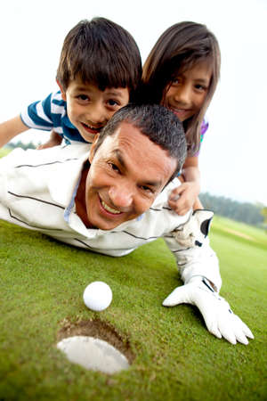 Family laying on the golf course next to the whole Stock Photo - 12198162