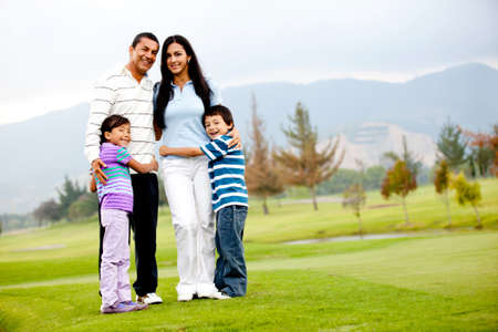 latin: Beautiful family outdoors in a green field  Stock Photo