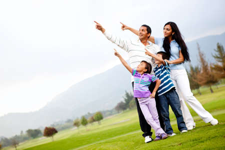 kid pointing: Beautiful family outdoors in a green field pointing