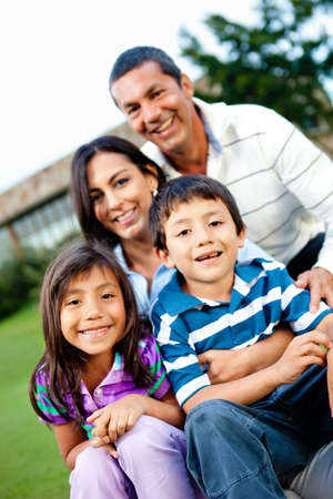 them: Happy family outdoors with their house behind them  Stock Photo