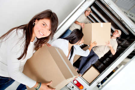 roommates: Girls moving house and unloading boxes from a truck Stock Photo