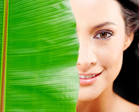 natural face: Woman portrait with a leave covering her face - natural beauty concepts