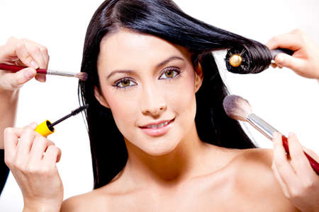 long dark hair: Woman getting professional make up and hair - isolated over a white background