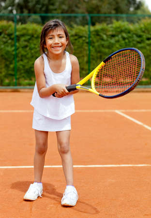 Girl playing tennis holding a racket at the court photo