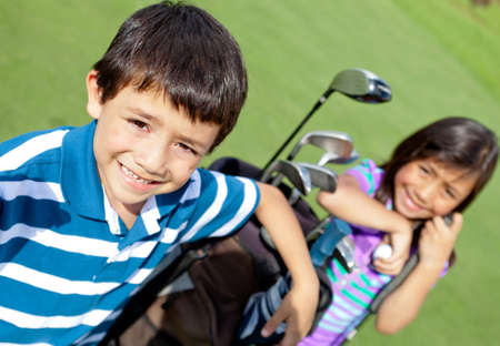 children playing outside: Kids playing golf and holding a bag at the course