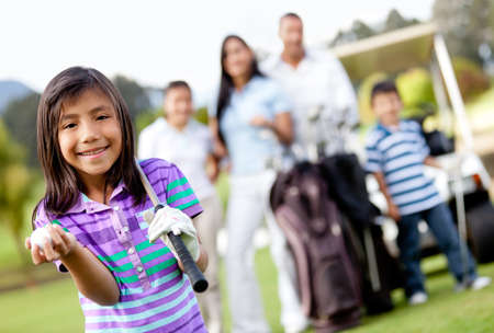 Beautiful girl at the course with her family playing golf  photo
