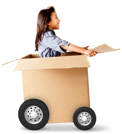 Girl in a car made of cardboard box - delivery on wheels photo