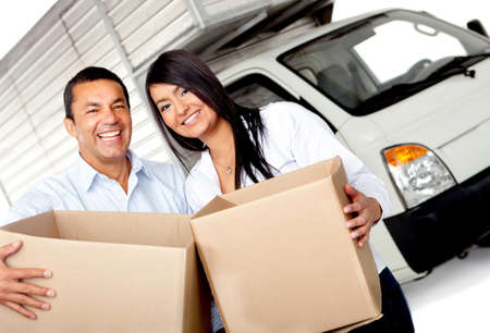 Couple moving house carrying boxes with a truck behind photo