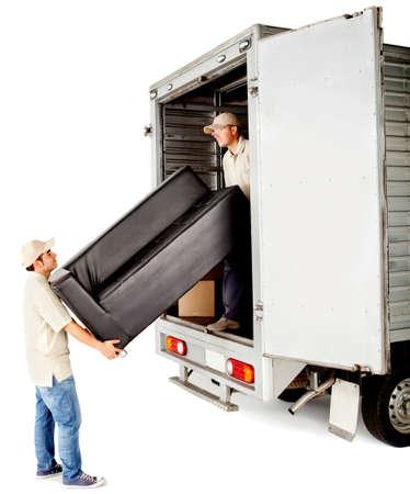 trasloco: Gli uomini di consegna con scarico di un divano da un camion - isolato su bianco