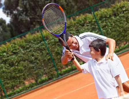 jugando tenis: Padre ense�ando a su hijo c�mo jugar al tenis Foto de archivo