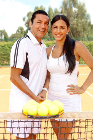 Couple of tennis players at the court holding a racket and balls photo