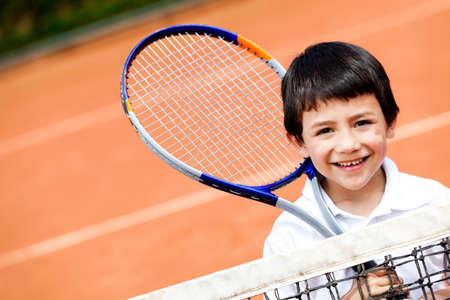 nios hispanos: Ni�o jugando al tenis en una cancha de arcilla